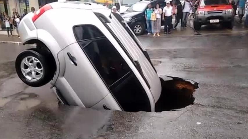 لحظة سقوط سيارة داخل حفرة عملاقة وسط الطريق  (فيديو)